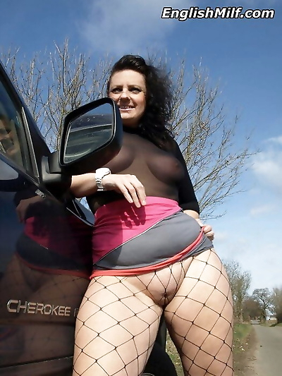 Fatty mature MILF Daniella English flashes naked upskirt in fishnet outdoors